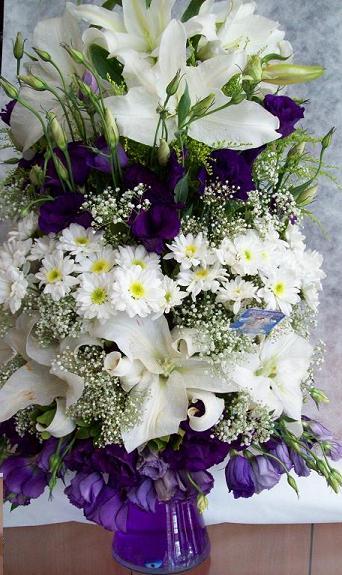 Beyaz lilyumlar ve mor lisyantuslar ile hazırlanmış cam vazo aranjman