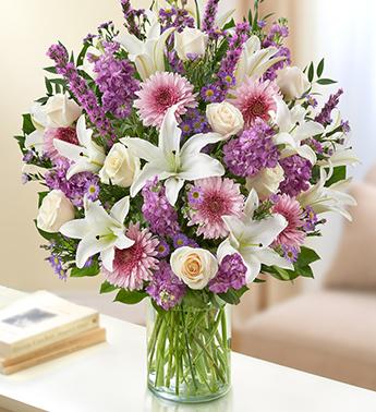 Beyaz lilyum cerbera ve güllerden hazırlanmış cam vazo aranjman