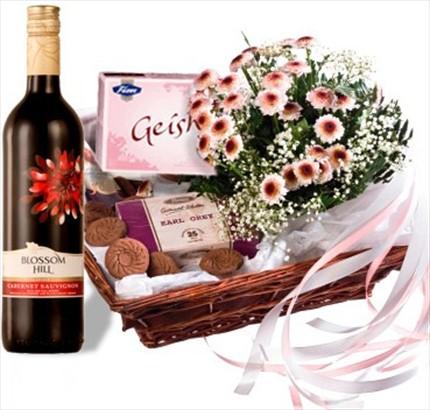 Kırmızı şarap ve tatlılar ile hazırlanmış hediye sepeti