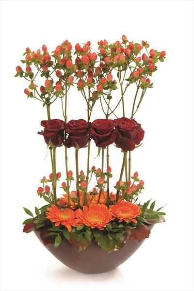 Oval vazo içerisinde kırmızı ve turuncu çiçek aranjmanı
