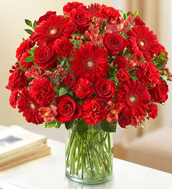 Cam vazo içerisine kırmızı gül ve mevsim çiçeklerinden hazırlanmış aranjman