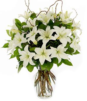 Beyaz lilyumlardan hazırlanmış cam vazo aranjman