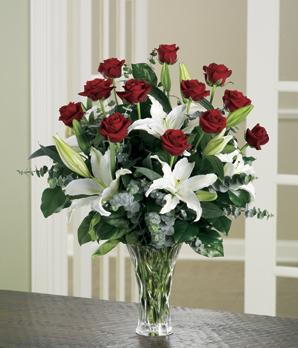 Beyaz lilyumlar ve kırmızı güller ile hazırlanmış cam vazo aranjman