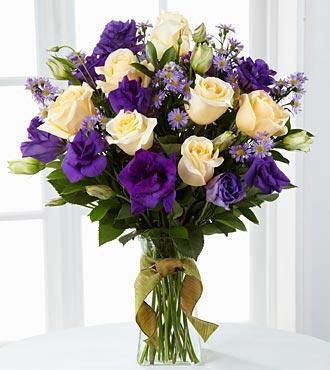 Cam vazoda beyaz güller ve mor mevsim çiçeklerinden aranjman