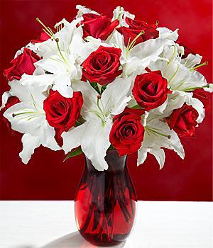 Cam vazoda kırmızı güller ve beyaz lilyumlardan aranjman