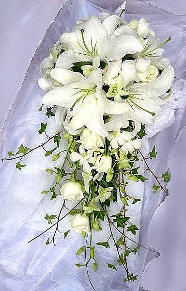 Beyaz lilyumlar güller ve özel yeşilliklerle hazırlanmış buket