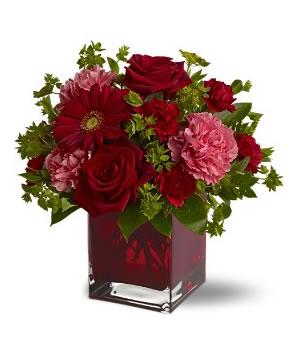 Kare vazo içerisine kırmızı su ile hazırlanmış mevsim çiçekleri aranjmanı